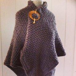 MM017 - Vierkant gebreide omslag doek, vast te maken met losse houten speld. Kleur: bruin.